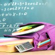 Purple backpack with school supplies on wooden table on green desk background — Stock Photo #35697397
