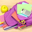 Purple backpack with school supplies on wooden background — Stock Photo #35697405