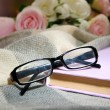 Stock Photo: Composition with old book, eye glasses, candles and plaid on dark background