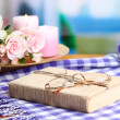 Composition with old book, eye glasses, candles, flowers and plaid on bright background — Stock Photo #35697451