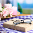 Composition with old book, eye glasses, candles, flowers and plaid on bright background — Stock Photo #35697453