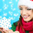 Beautiful smiling girl with Christmas snowflake on blue background — Stock Photo
