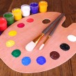 Wooden art palette with paint and brushes on table close-up — Foto Stock
