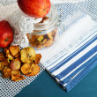 Dried apples in glass jar, on color wooden background — ストック写真