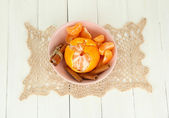 Tasty mandarines in color bowl on light background — Stock Photo