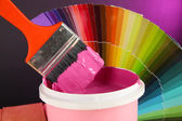Paint pot, paintbrush and coloured swatches close up — Stock Photo