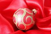 Beautiful Christmas ball on red satin cloth — ストック写真