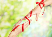 Mans and girls hands tied with ribbon on bright background — Stock Photo