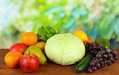 Verschiedene früchte und gemüse auf tabelle auf hölzernen hintergrund — Stockfoto