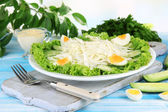 Delicious salad with eggs, cabbage and cucumbers on blue wooden table — Stock Photo