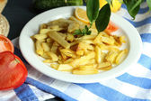 Ruddy fried potatoes on plate on tablecloth close-up — Foto de Stock