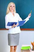 School teacher with folder near blackboard in classroom — Stock Photo