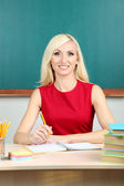 School teacher sitting at table on blackboard background — Stock Photo