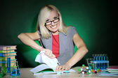 Wicked chemistry teacher sitting at table on dark colorful background — Стоковое фото