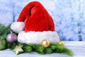 Composition with Santa Claus red hat and Christmas decorations on light background — Stock fotografie