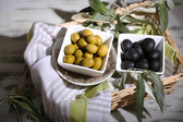 Olives in bowls with branch on napkin in basket on wooden table — Stock Photo