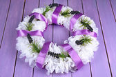Decorative wreath with flowers on wooden background — Stock Photo