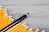 Celebratory pencil among usual pencils, on color background — Stock Photo