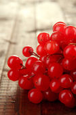 Red berries of viburnum on wooden background — Stock Photo