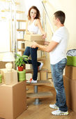 Young couple with boxes in new home on staircase — Stock Photo
