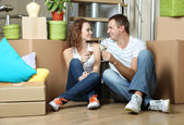 Young couple celebrating moving to new home sitting among boxes — Stock Photo