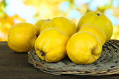 Sweet quinces on table on bright background — Stock Photo
