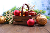 Composition with Christmas decorations in basket, fir tree on wooden table, on light background — Stockfoto
