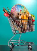 School supplies in supermarket cart on blackboard background — Stock Photo