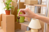 Female hand with keys ob stack of cartons background: moving house concept — Stock Photo