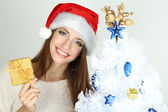 Beautiful smiling girl near Christmas tree with gift — Stock Photo