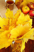 Bright autumn leafs in vase on wooden table close-up — Stock Photo