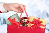 Main tient un paquet avec des boules de nouvel an et des cadeaux sur fond de neige — Photo