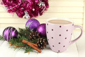 Cup of hot cacao with bumps and Christmas decorations on table on wooden background — Photo