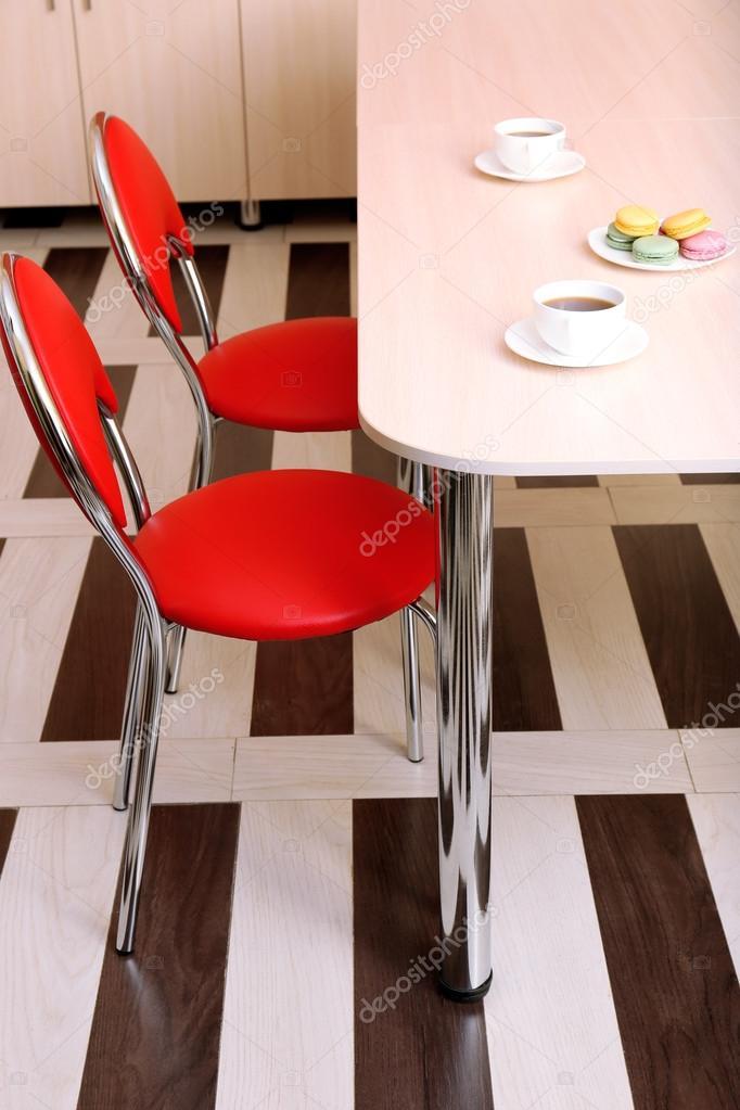 Moderne rode stoelen in de buurt van tafel in keuken — stockfoto ...