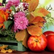 Stock Photo: Flowers composition in crate with apples on table on bright background