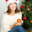 Beautiful smiling girl sitting near Christmas tree in room — Stock Photo #35827219