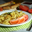 Stock Photo: Ruddy fried potatoes on plate on wooden table close-up