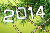 2014 hang on Christmas tree close-up on green background — Stock Photo