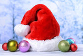 Composition with Santa Claus red hat and Christmas decorations on light background — Stock Photo