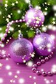 Christmas balls on fir tree, on color background — Stock Photo
