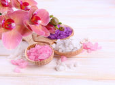 Orchid flower and wooden spoons with sea salt — Stock Photo