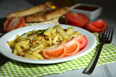 Ruddy fried potatoes on plate on wooden table close-up — Zdjęcie stockowe