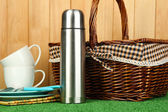 Thermos with cups, plates and basket on grass — Stock Photo