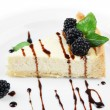 Slice of cheesecake with chocolate sauce and blackberry on plate, isolated on white — Stock Photo #35836597