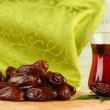 Dried dates with cup of tea on table on fabric background — Stock Photo