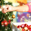 Decorating Christmas tree on bright background — Stock Photo #35837805