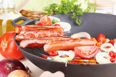 Delicious sausages with vegetables in wok on wooden table close-up — Stock Photo