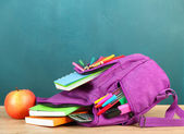 Backpack with school supplies on table — Stock Photo