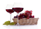 Wineglasses with red wine and grape in wicker basket isolated on white — Stock Photo