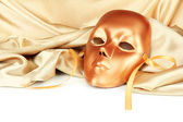 Mask on gold fabric — Stock Photo